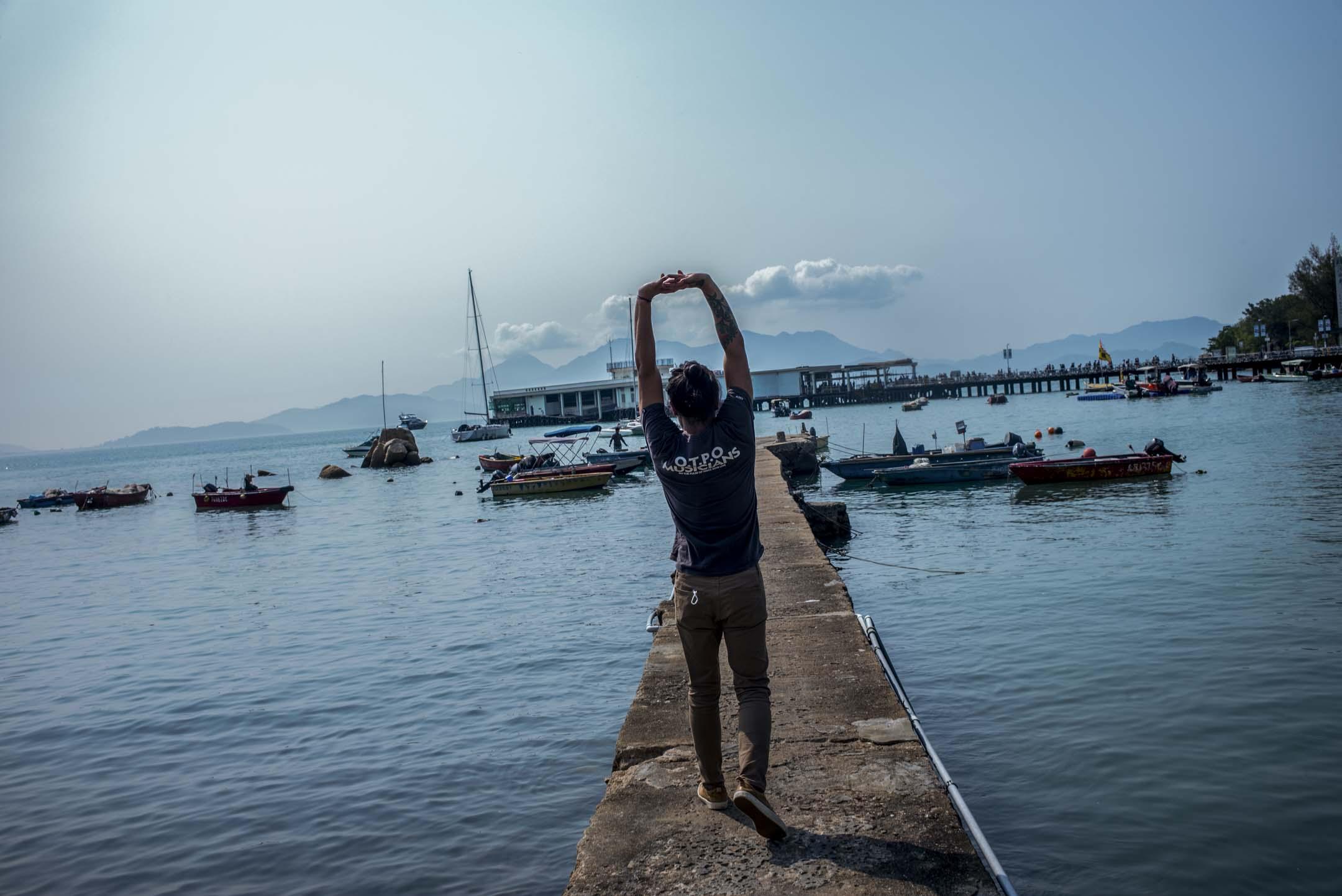 黑鬼在南丫島榕樹灣的小碼頭上伸展筋骨。 攝:林振東/端傳媒