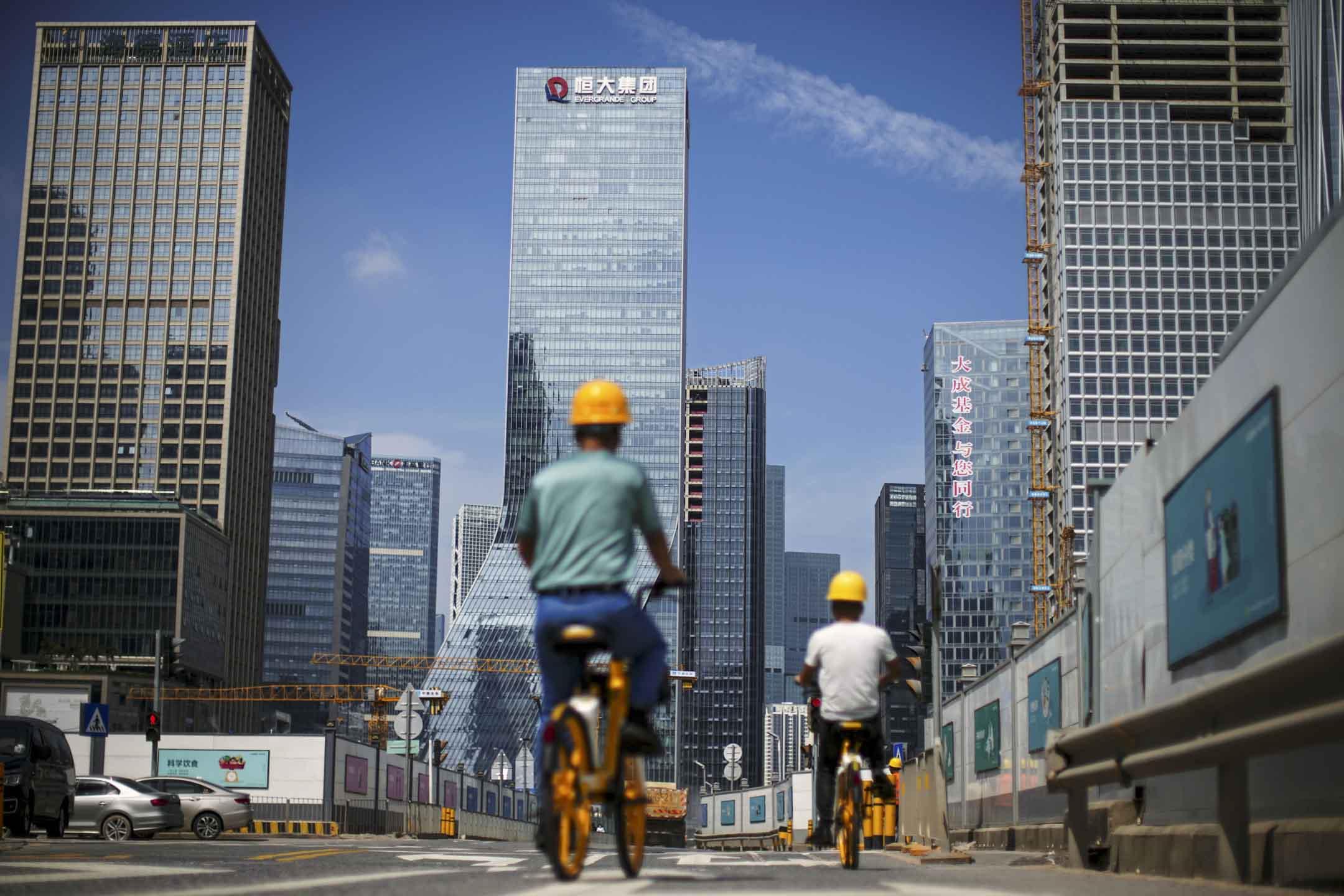 2021年9月26日,男子騎單車經過深圳市恆大集團總部附近的建築工地。