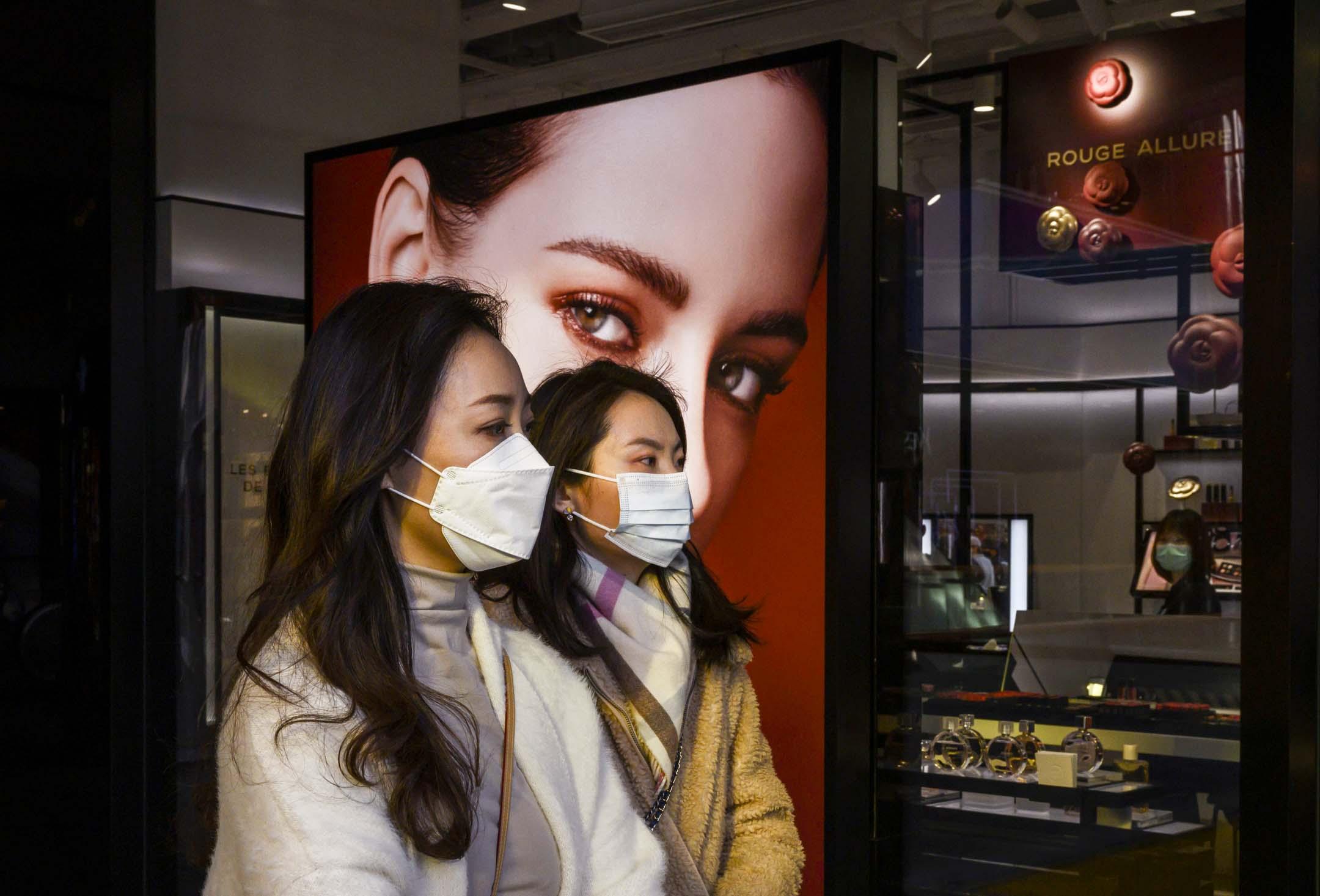 2020年3月10日,北京三里屯,兩名戴著防護口罩的女士路過一家奢侈品店。 攝:Kevin Frayer/Getty Images