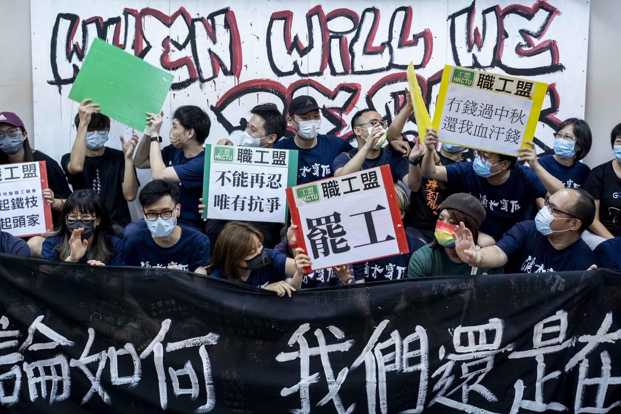 2021年10月3日,職工盟解散記者會後,幹事們聚集高呼工盟歷年口號,並展示部份示威牌。 攝:林振東/端傳媒