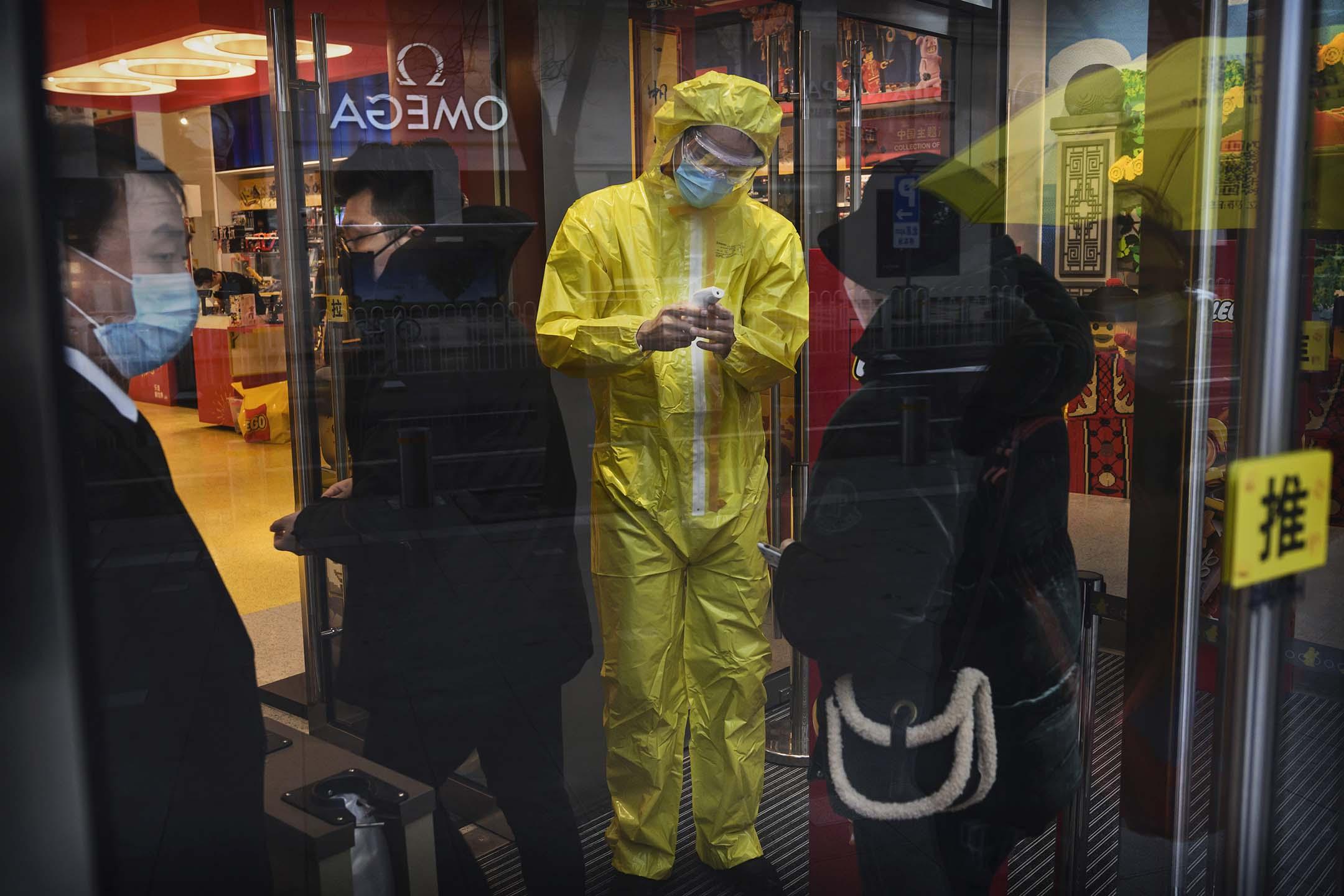 2020年2月14日中國北京,一名工作人員穿著防護衣在北京的一個購物區檢查顧客的體温。
