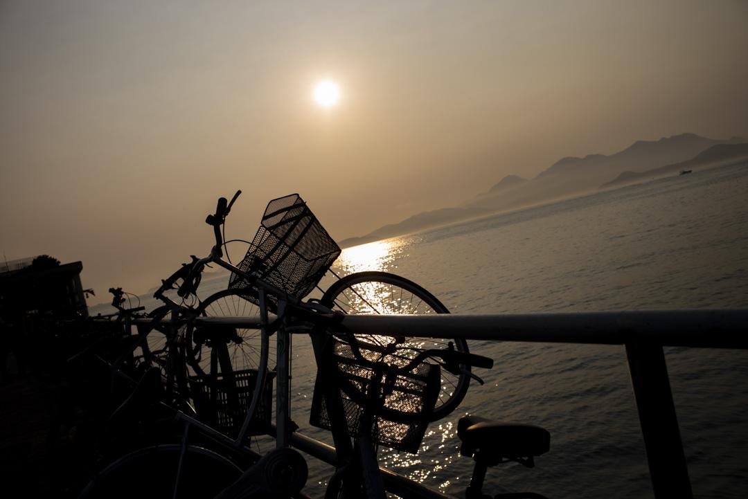 夕陽下,一架單車架在榕樹灣碼頭旁的欄杆上。