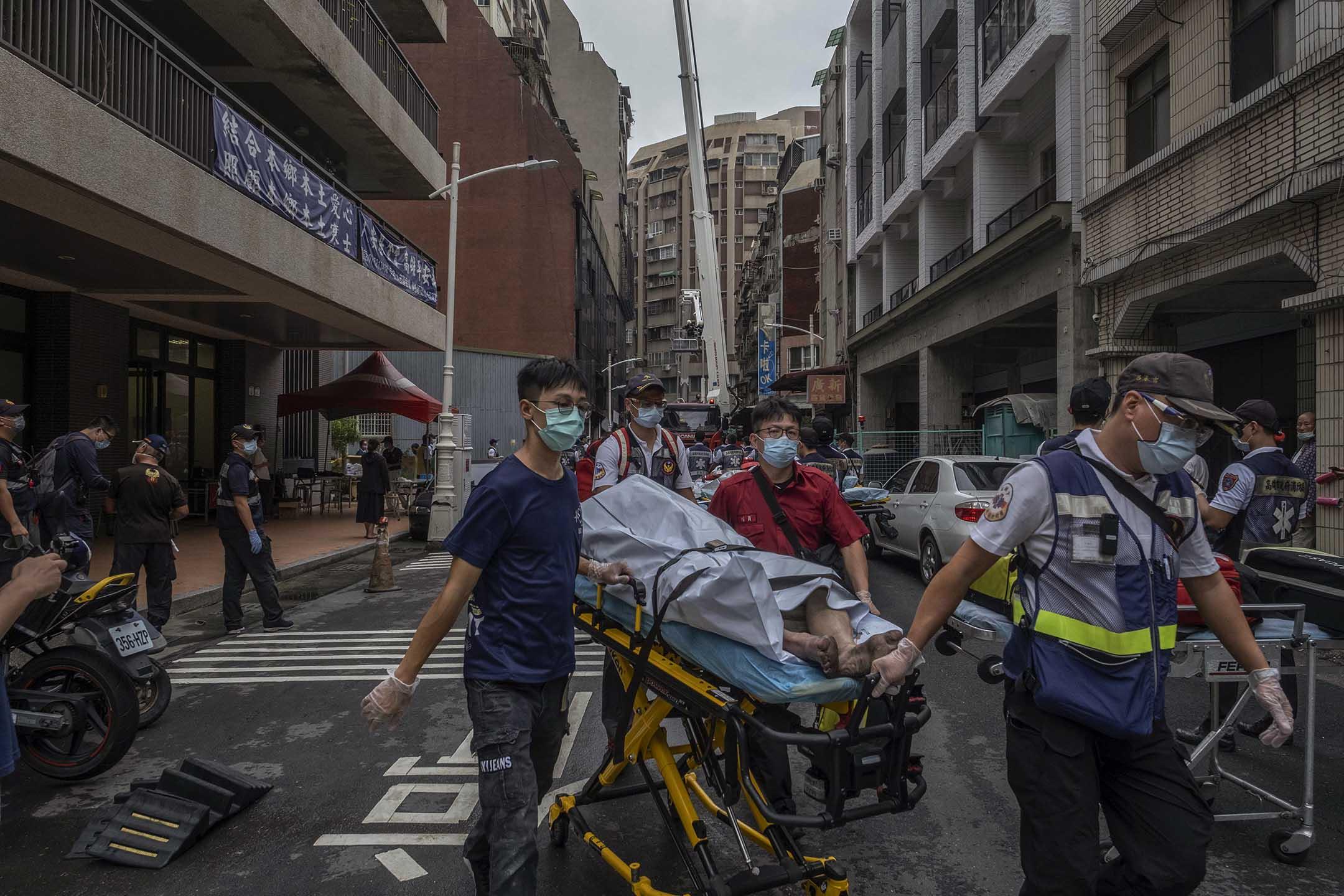 2021年10月14日台灣高雄發生火災後,醫護人員從災場運送一具屍體。